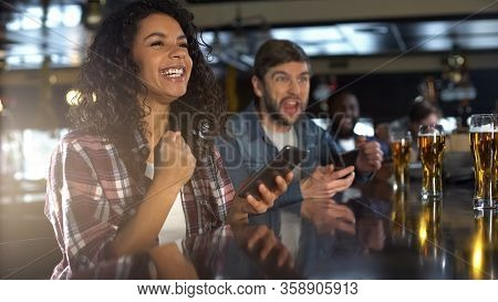 Smiling Biracial Woman In Pub Celebrating Winning Sports Bet, Bookmaker App