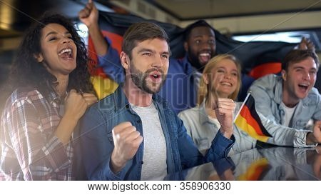 Enthusiastic German Sports Fans Holding Flag, Happy About National Team Victory