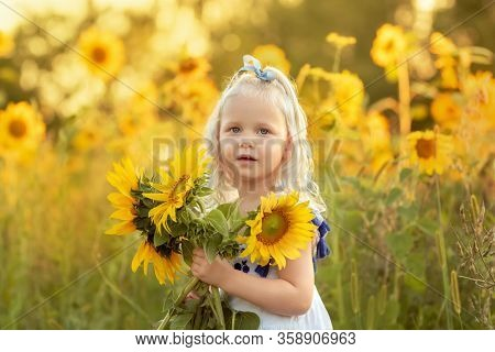 Portrait of a little girl with a bouquet of sunflowers