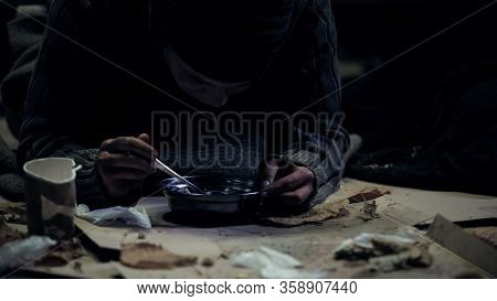 Homeless Person Greedily Eating Soup From Steel Bowl, Dirty Shelter, Famine