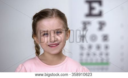 Adorable Child Girl Laughing After Vision Test On Eye Chart, Healthy Sight