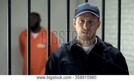 Warden Looking At Camera In Prison, African American Criminal On Background