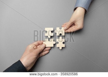 Two Hands Connect Puzzles On A Grey Background. Cooperation And Teamwork In Business. Collaboration