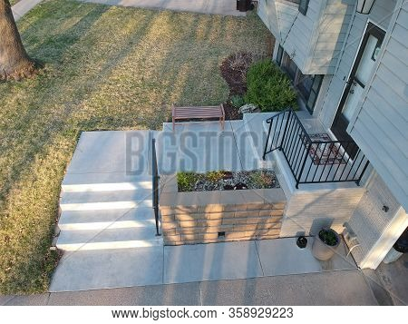 Elevated View Of A Split Level Home Remodel With New Concrete Entrance With Flower Planter & Railing