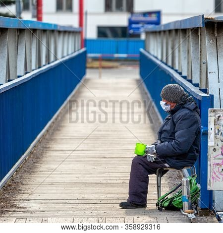 Ruzomberok, Slovakia - March 31, 2020: Beggar With Face Mask On Footbridge