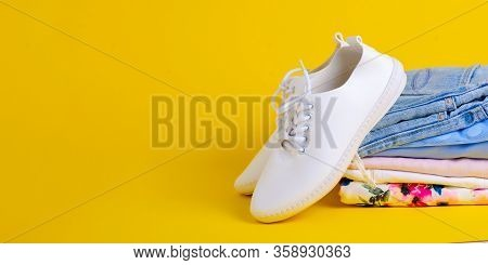 Stack Folded Colorful Clothing Summer And White Sneakers On Yellow Background