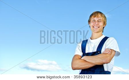 Smiling Handyman In Coveralls On Sky Background