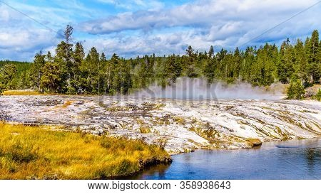 Hot Water From The Oblong Geyser Flowing Into The Firehole River In The Upper Geyser Basin Along The