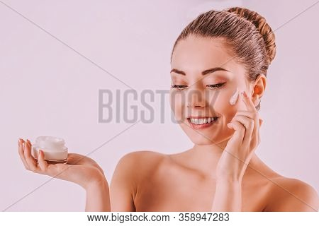 Attractive Girl Applying Moisturizing Lotion On Face And Smiling. Beautiful Young Woman With Perfect