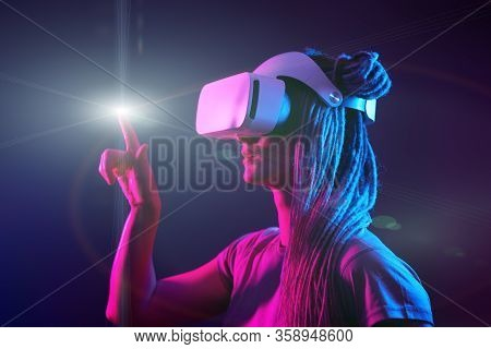 Woman Is Using Virtual Reality Headset. Neon Light Studio Portrait. Concept Of Virtual Reality, Simu
