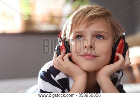 Cute Little Boy With Headphones Listening To Audiobook At Home