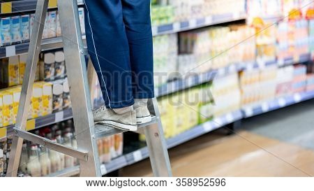 Male Storekeeper Legs Standing On Aluminum Stair Putting Products On Shelves In Grocery Store Or Sup