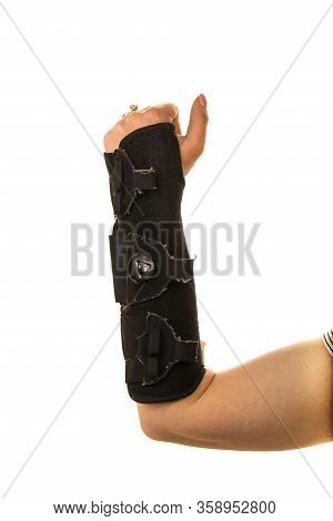 Close Up Of Woman Hand In Orthosis Raised Up Isolated On White Background