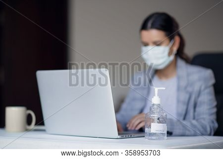 Young Female Employee In Medical Protective Mask From Corona Virus Covid-19 Working On Laptop At Wor