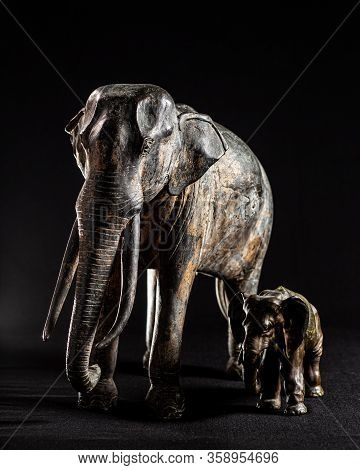 Studio Shot Of Antique Metallic Elephant Figurines On A Black Background With Dramatic Lighting