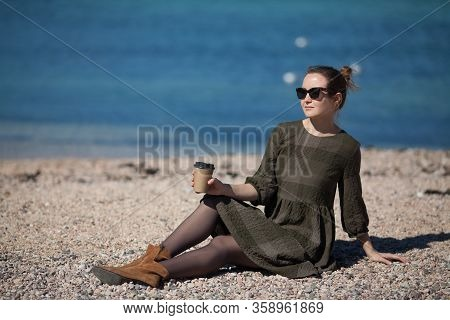 A Beautiful Pretty Girl Is Sitting On The Beach By The Sea And Drinking Coffee To Take Away . The Co