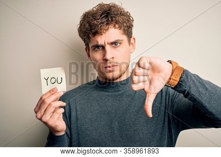 Young blond man with curly hair holding paper with you message over white background with angry face, negative sign showing dislike with thumbs down, rejection concept
