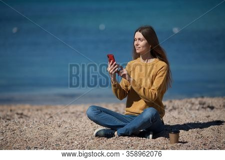 Beautiful Fashionable Girl Writes Sms On Her Smartphone On The Beach On The Sea. The Concept Of Tech