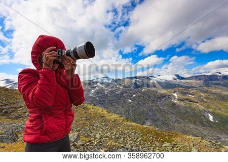 Female Tourist Taking Photo With Camera, Enjoying Mountains Landscape From Dalsnibba Area In Norway.
