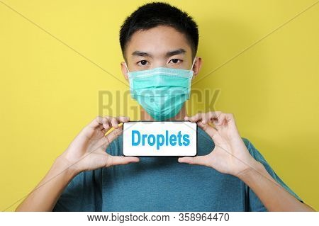 Young Asian Man Wearing Protect Mask Showing Droplets Text On Phone Screen, Isolated On Yellow Backg