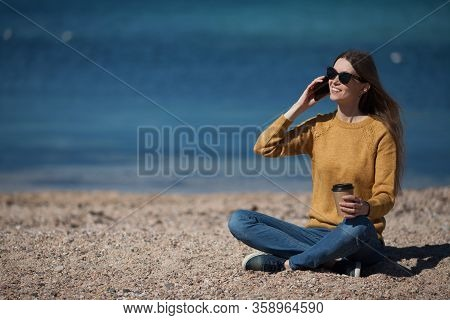 A Beautiful Girl Is Talking On Her Mobile Phone And Holding A Takeaway Coffee In Her Hand On The Bea
