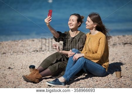 Two Friends Of The Girl Travel Together And Take A Selfie On Their Smartphone. The Concept Of Travel