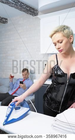 Vertical Shot, A Woman In A Leather Corset Is Ironing Clothes, A Man Is Sitting On A Sofa. Humor, Ir