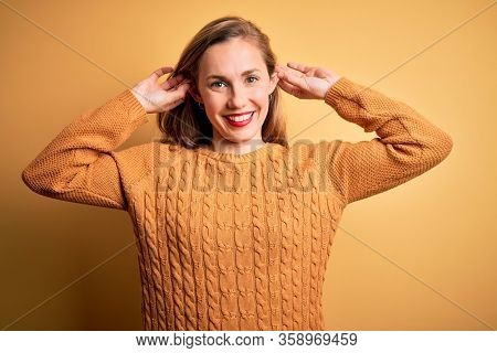 Young beautiful blonde woman wearing casual sweater standing over yellow background Smiling pulling ears with fingers, funny gesture. Audition problem