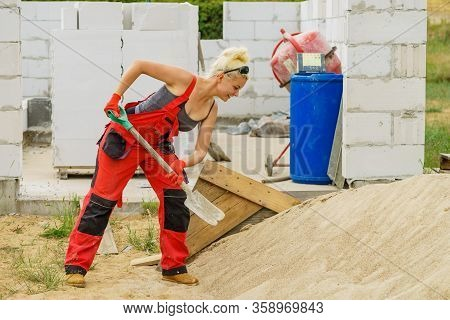 Woman Using Shovel On Constriction Site