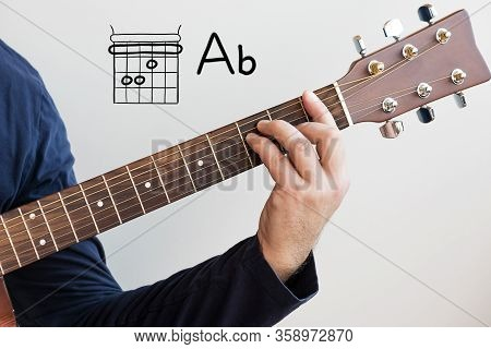 Learn Guitar - Man In A Dark Blue Shirt Playing Guitar Chords Displayed On Whiteboard, Chord A Flat