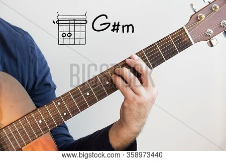 Learn Guitar - Man In A Dark Blue Shirt Playing Guitar Chords Displayed On Whiteboard, Chord G Sharp