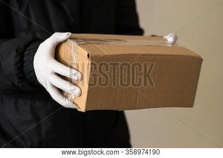 Girl Courier Holds A Parcel In Protective Gloves. Epidemic. Close-up