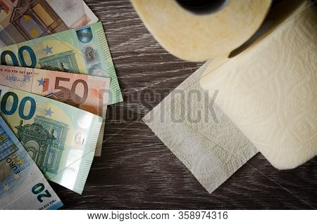Euro Bills And Toilet Paper On Wooden Background. Close-up