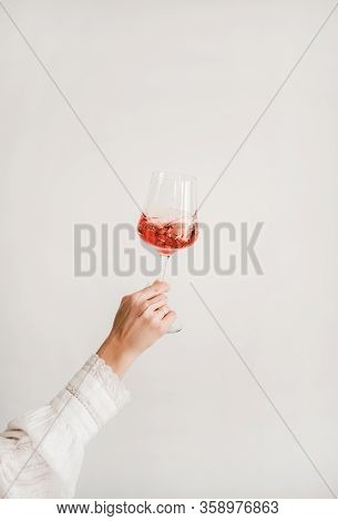 Womans Hand Holding And Turning Glass Of Rose Wine