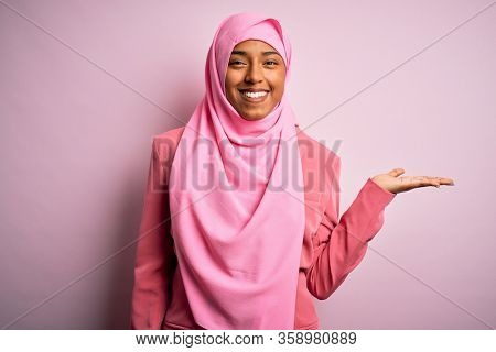 Young African American afro woman wearing muslim hijab over isolated pink background smiling cheerful presenting and pointing with palm of hand looking at the camera.