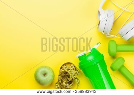 Fitness equipment on a yellow background. Top view flat lay with copy space for workout plan