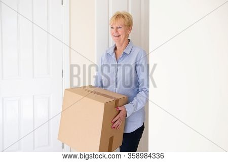 Senior Woman Downsizing In Retirement Carrying Boxes Into New Home On Moving Day