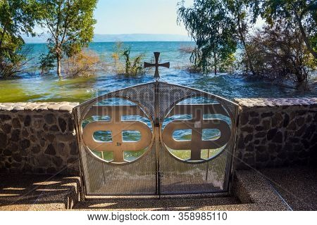 The small beautiful gate that closes the descent to the water of the Sea of Galilee. The Monastery of the Holy Twelve Apostles, Capernaum. Israel.  The concept of religious pilgrimage and photo touris