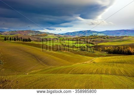 Picturesque hills of the legendary Tuscany. Agritourism. Rural farms. Smooth rows of plowed fields and meadows. Beautiful Italy. The concept of active, rural and photo tourism