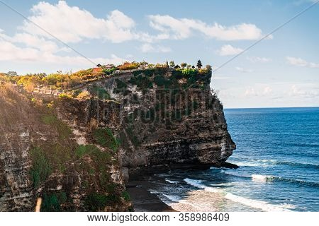 Uluwatu Temple At Dawn. The Sheer Cliffs Of The Southern Coast Of Bali Are Washed By A Clear Azure O