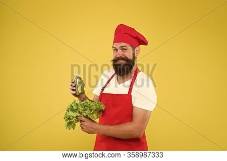 Greenery In Bottle. Fresh Juice. Squeezing Smoothie. Man Bearded Chef Hold Lettuce And Smoothie Bott