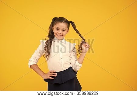 Her Twisted Hairdo. Small Girl Winding Long Hairdoaround Her Finger On Yellow Background. Little Kid
