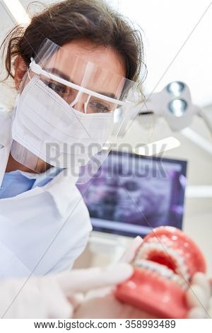 Woman as a dentist with surgical mask and visor explains the treatment on a denture model