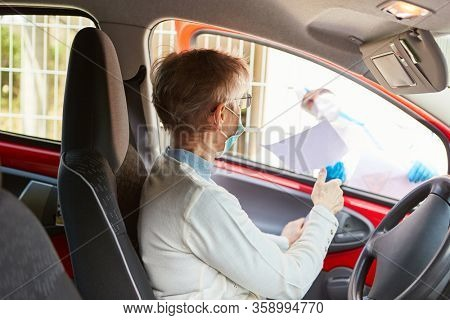 Elderly woman with face mask in the car at Coronavirus Drive-In test station for Covid-19 test