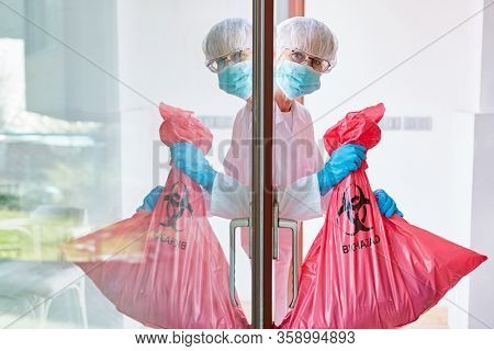 Waste disposal of infectious waste in clinic by cleaner in protective clothing during Covid-19 coronavirus epidemic
