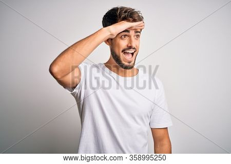 Young handsome man with beard wearing casual t-shirt standing over white background very happy and smiling looking far away with hand over head. Searching concept.
