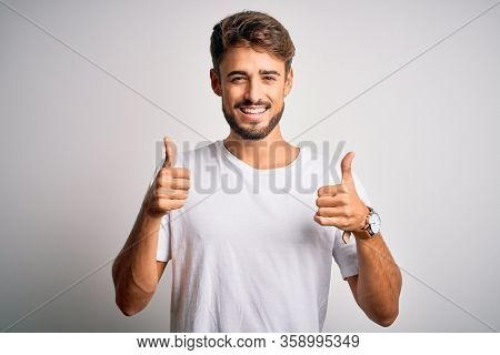 Young handsome man with beard wearing casual t-shirt standing over white background success sign doing positive gesture with hand, thumbs up smiling and happy. Cheerful expression and winner gesture.