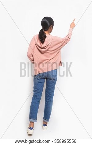 Back view Full length young woman in brown sweater with blue jeans young woman in brown shirts with white jeans isolated with hands and fingers to the side