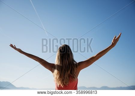 View From Behind Of A Young Woman With Long Hair Standing  Outside Under Clear Summer Sky With Her A