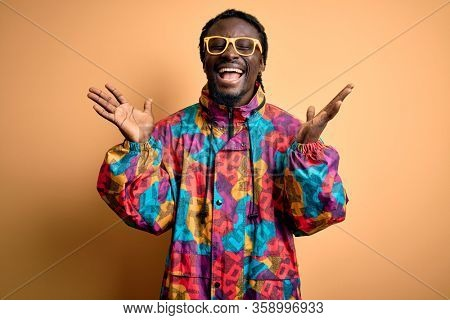 Handsome african american man wearing colorful coat and glasses over yellow background celebrating mad and crazy for success with arms raised and closed eyes screaming excited. Winner concept